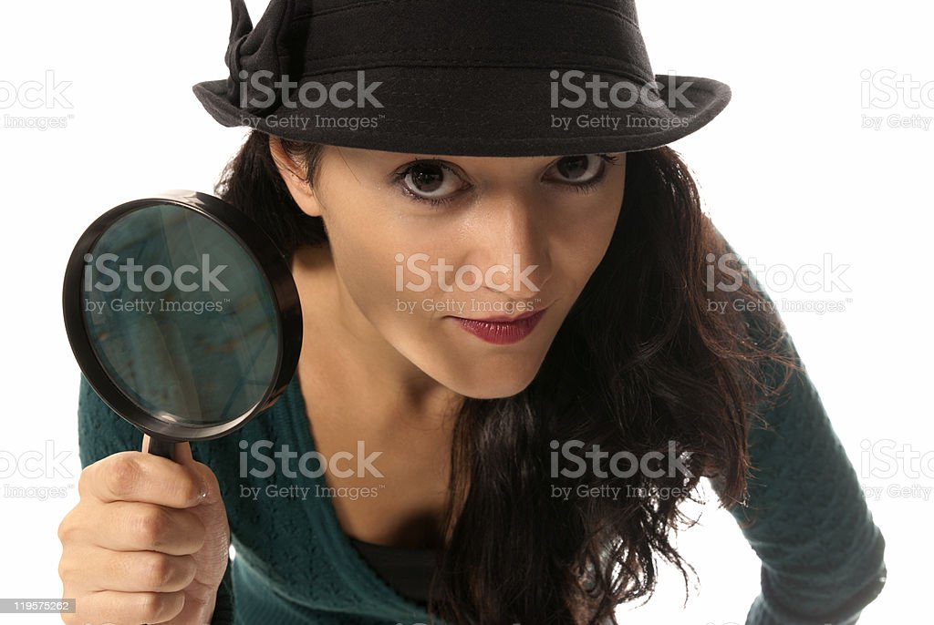 young woman with magnifier glass and hat looking to camera royalty-free stock photo
