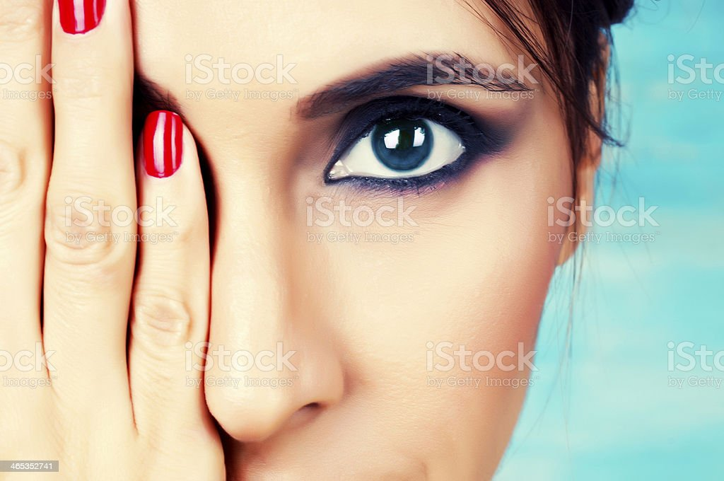 Young woman with make up on covering one eye stock photo