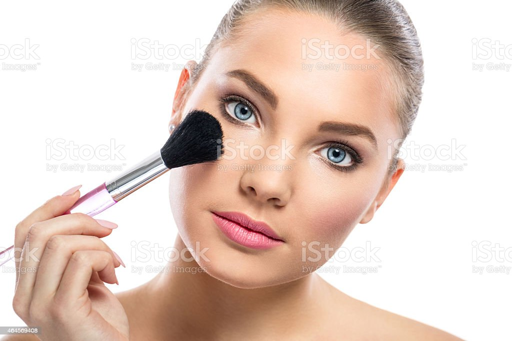 young woman with mirror applying powder on cheek stock photo