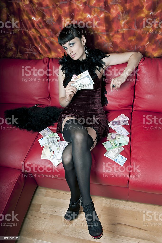 Young Woman with Money on Red Sofa royalty-free stock photo