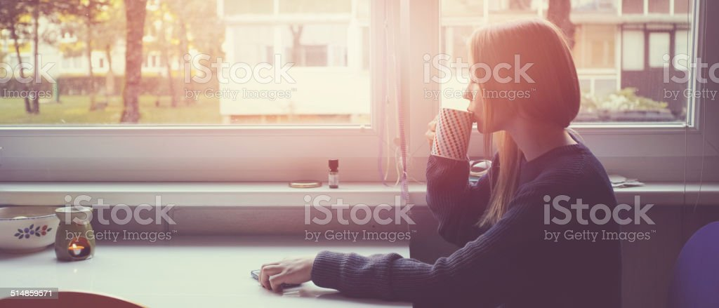 Young woman with morning cup of coffee near window stock photo