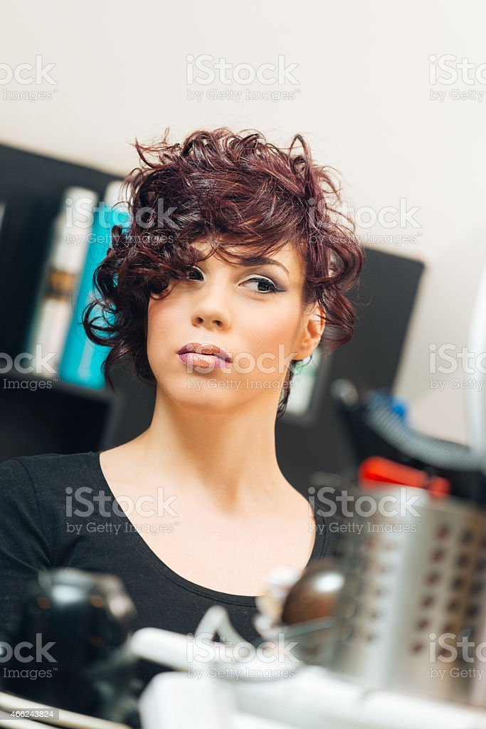 Young woman with new curly hair style in hair salon stock photo