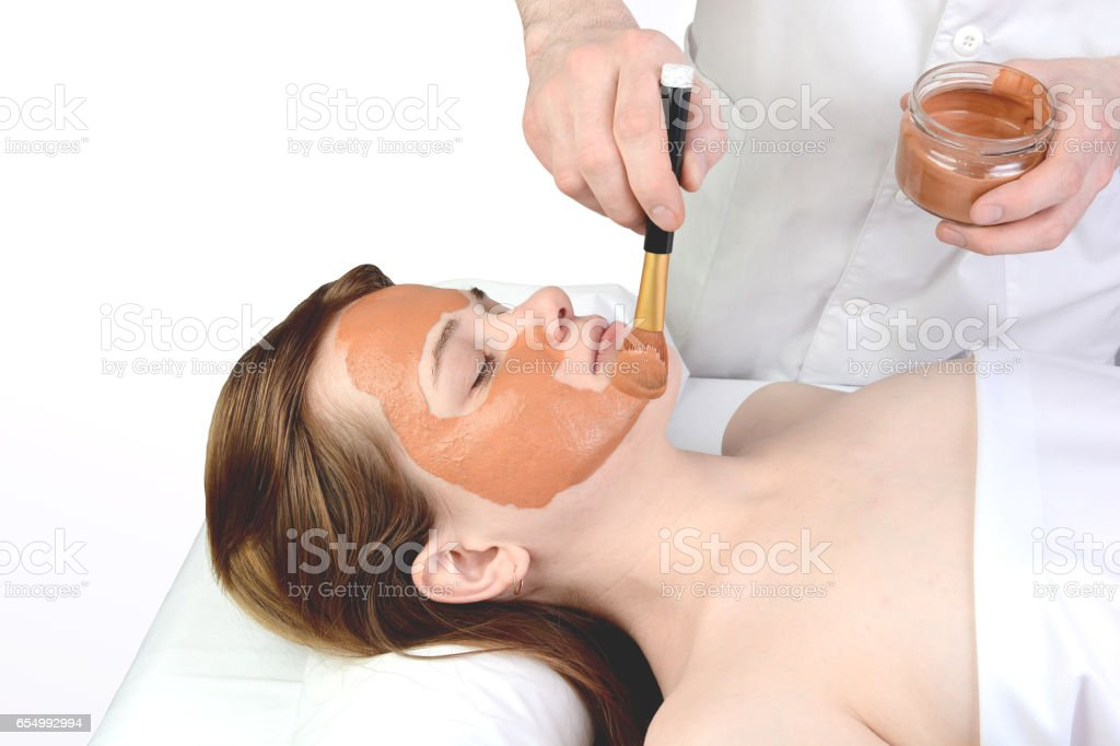 Young woman with nutrient facial mask in beauty salon stock photo