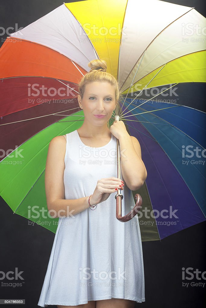 Young woman with open colorful umbrella. Color image stock photo