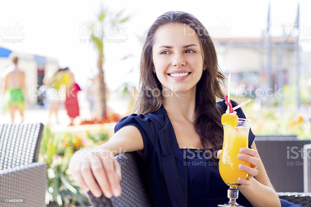 Young woman with orange juice sitting in summer cafe outdoors royalty-free stock photo