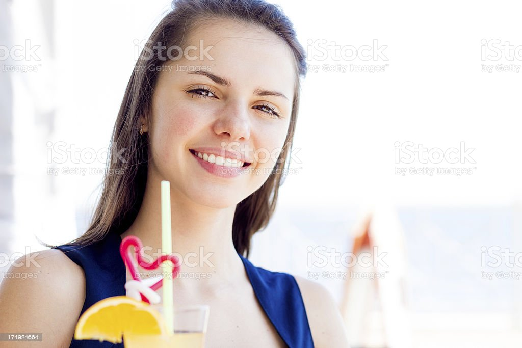 Young woman with orange juice smiling in summer cafe royalty-free stock photo