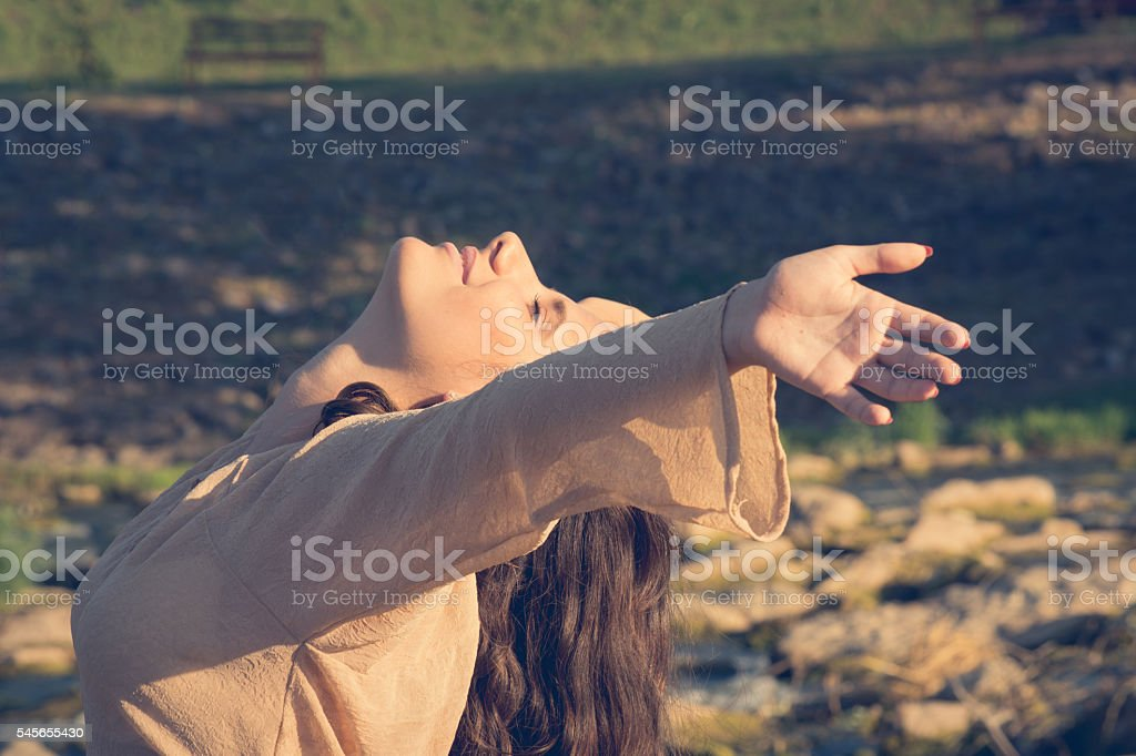 Young woman with outstretched arms enjoys in nature at sunset stock photo