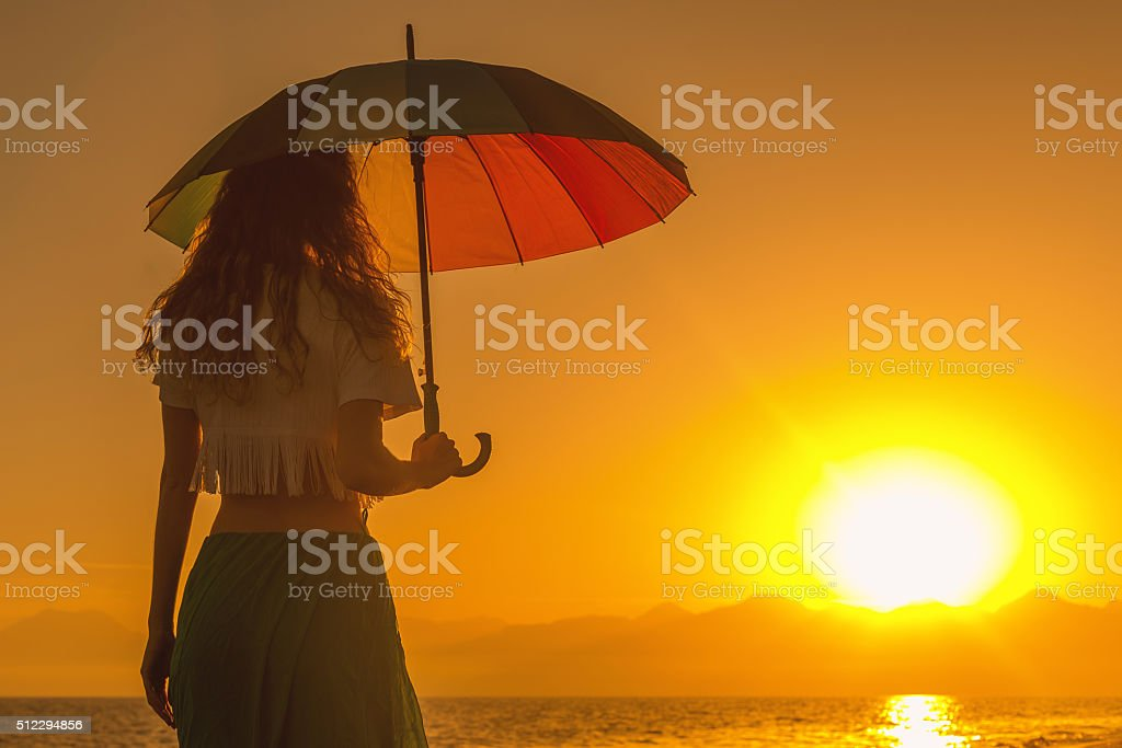 Young woman with parasol at sunset stock photo