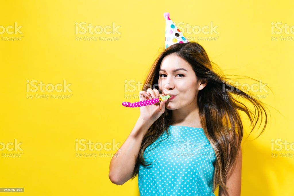 Young woman with party hat with noisemaker stock photo
