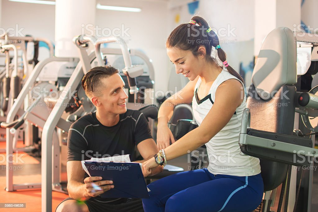 Young woman with personal trainer at gym. stock photo