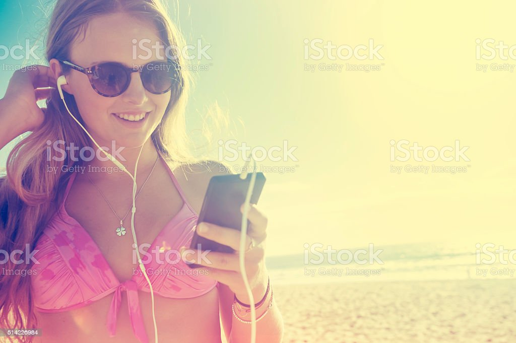 Young woman with phone and earphones at the beach stock photo