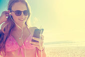 Young woman with phone and earphones at the beach