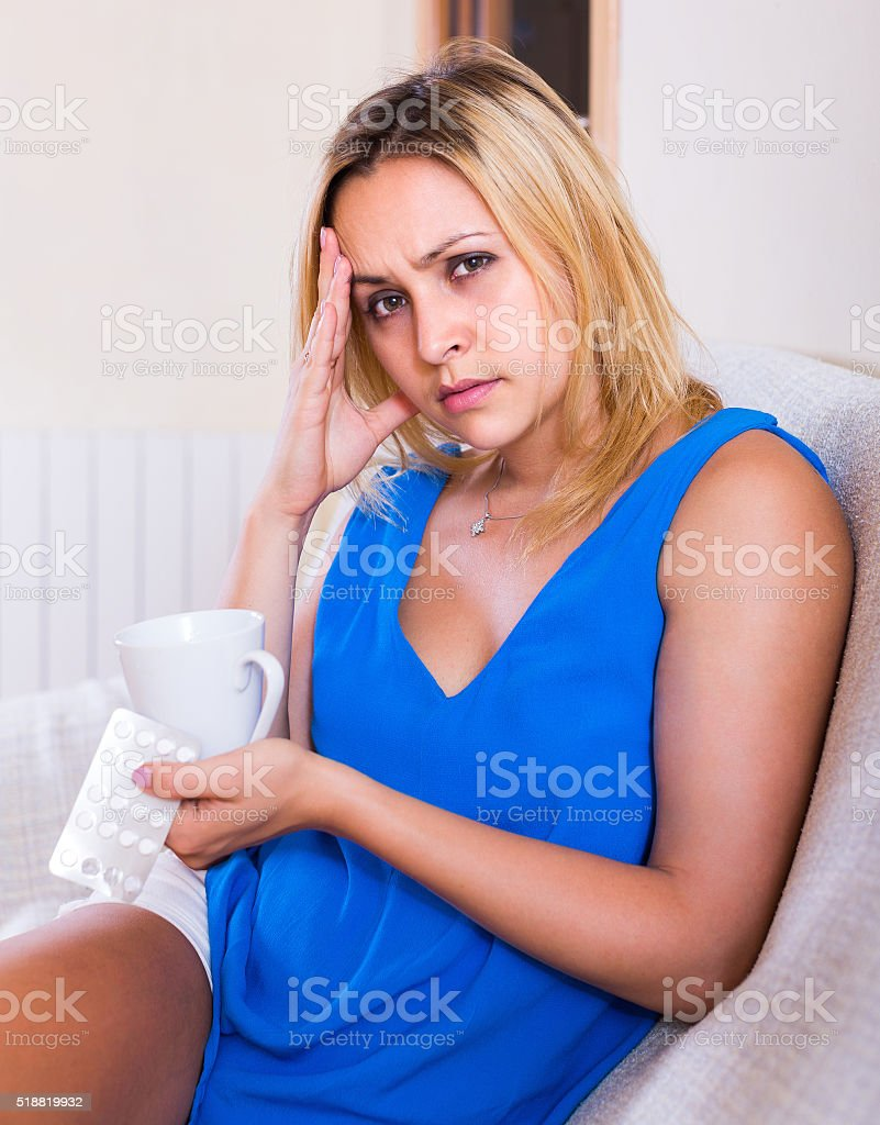Young woman with pills at home stock photo