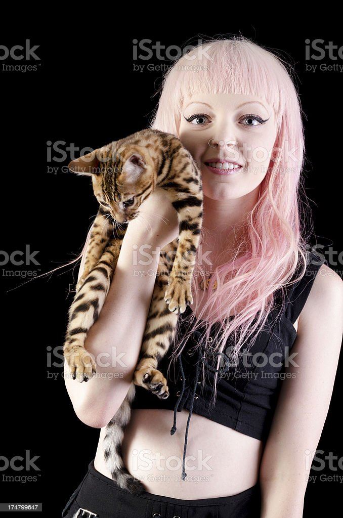 Young woman with pink hair holding Bengal kitten royalty-free stock photo
