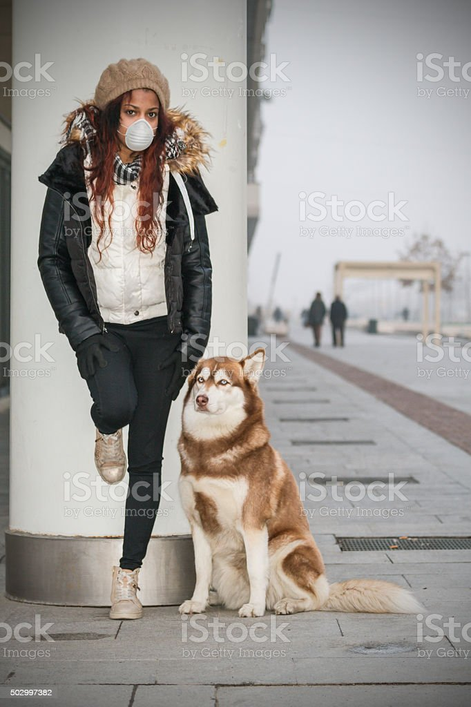 Young woman with pollution mask and her dog stock photo