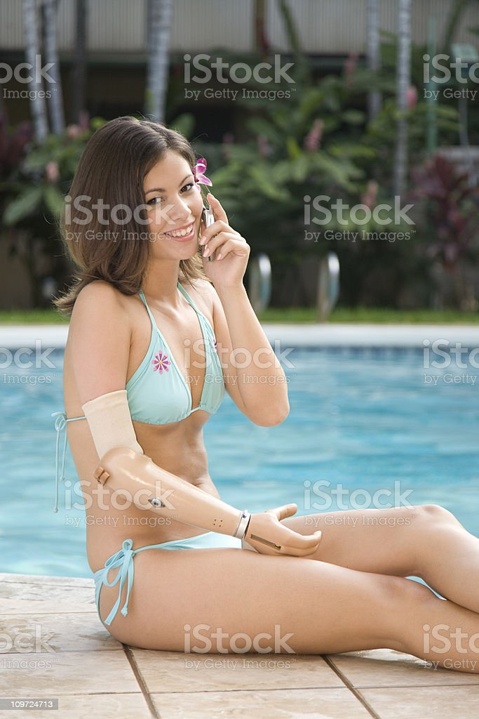 Young Woman with Prosthetic Arm and Cell Phone stock photo