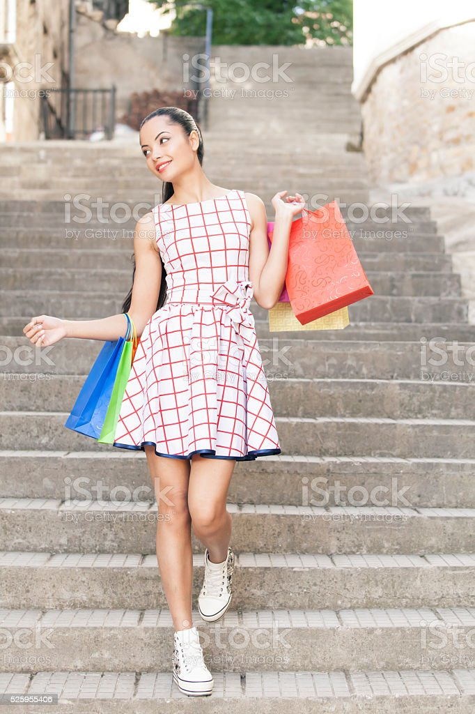Young woman with purcheses coming down stairs stock photo