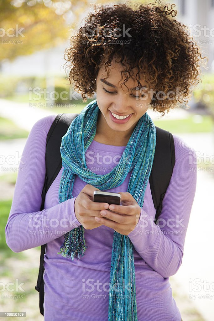 Young woman with purple top texting on a phone outdoors royalty-free stock photo