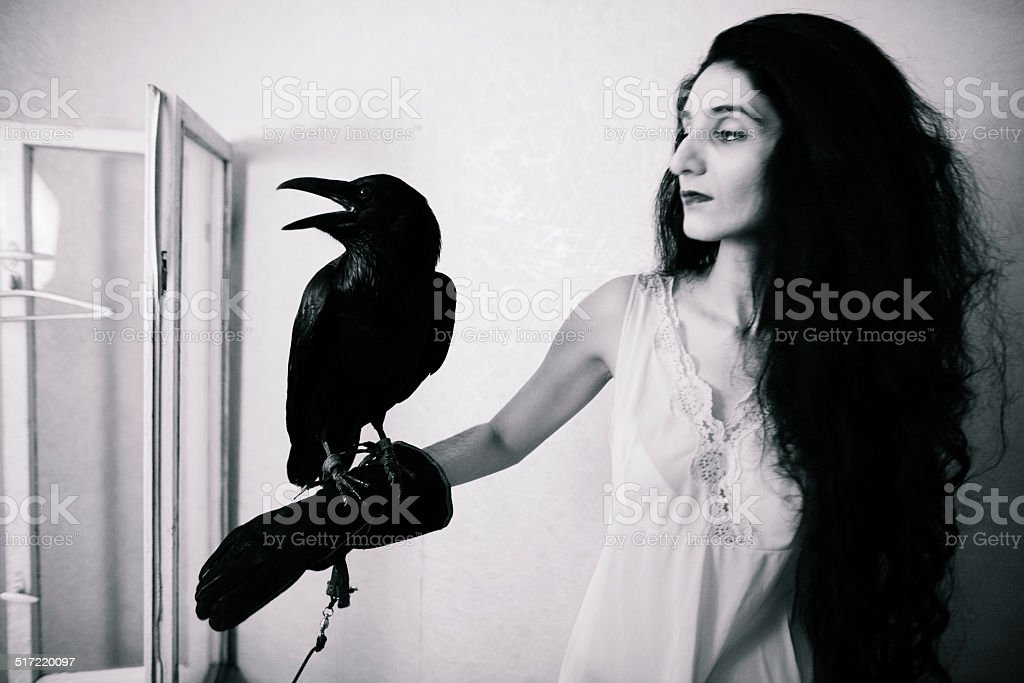 young woman with raven inside stock photo