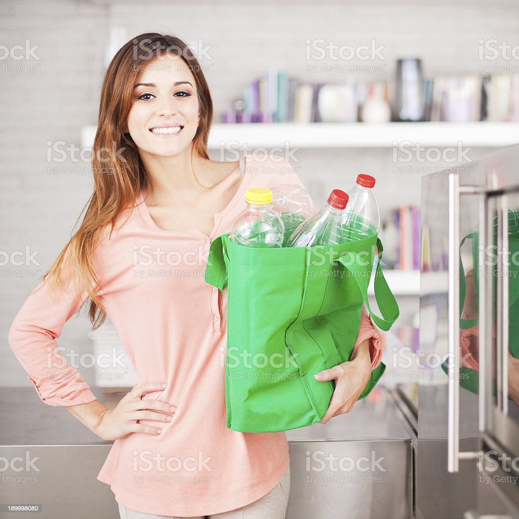 Young woman with recycling bag full of bottles stock photo