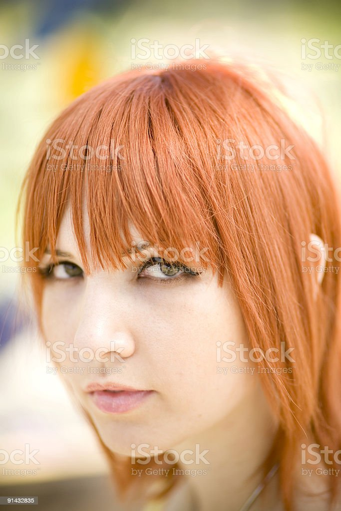 young woman with red hair and eyeliner looking at camera stock photo
