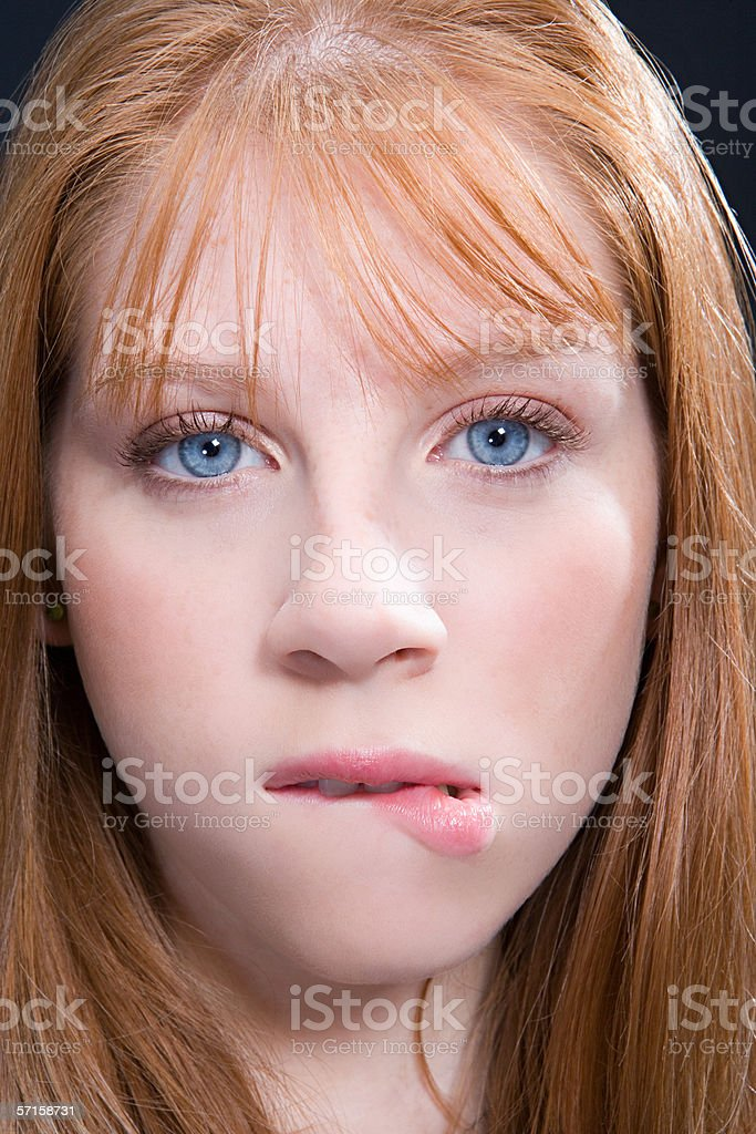 Young woman with red hair biting lip royalty-free stock photo