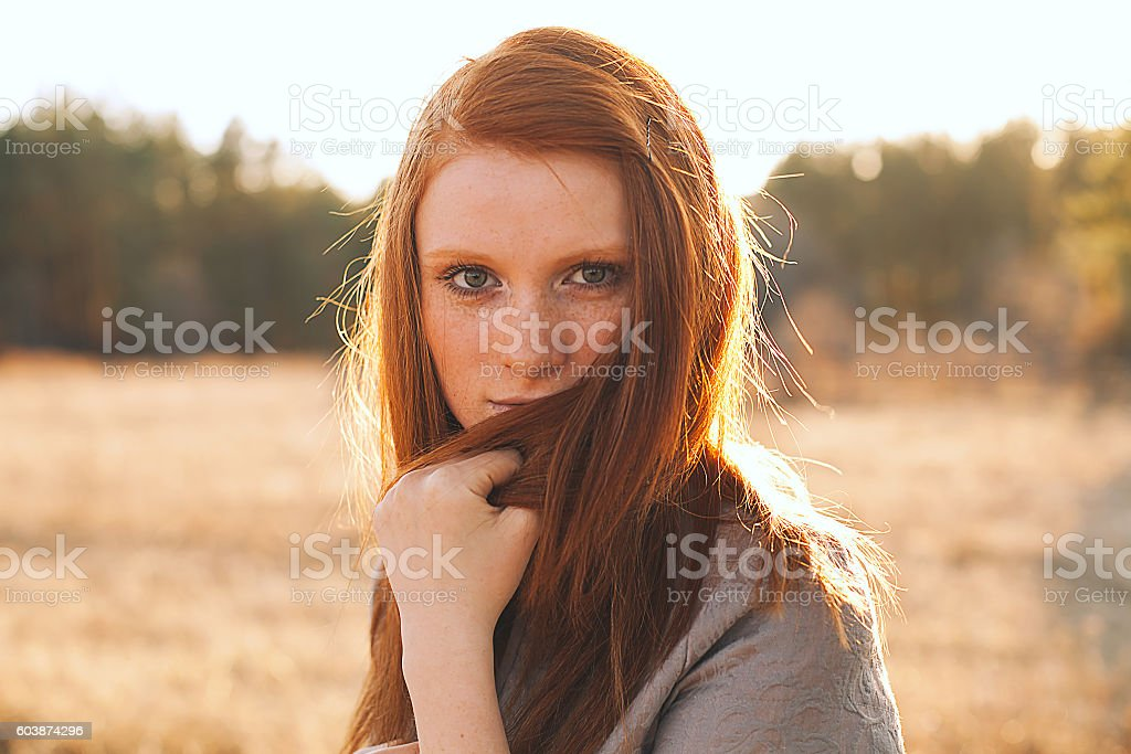 Young Woman with Red Hair in Golden Field at Sunset. stock photo
