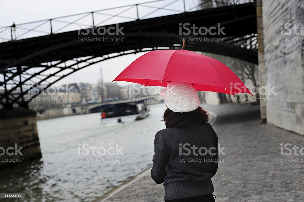 Young woman with Red Umbrella beside Seine River Paris France royalty-free stock photo