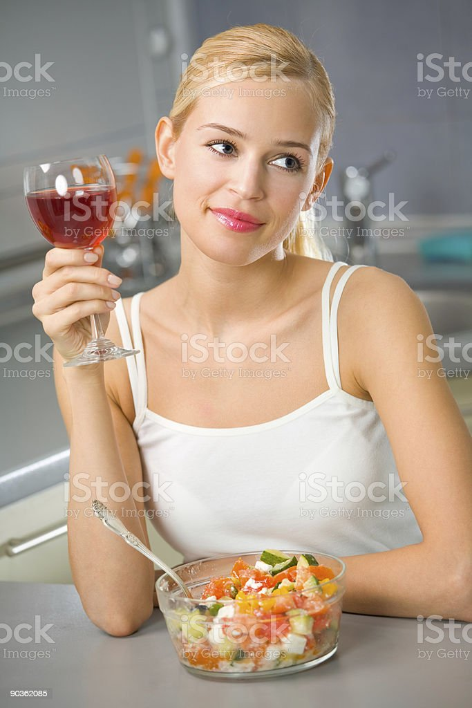 Young woman with red wine and salad at kitchen royalty-free stock photo