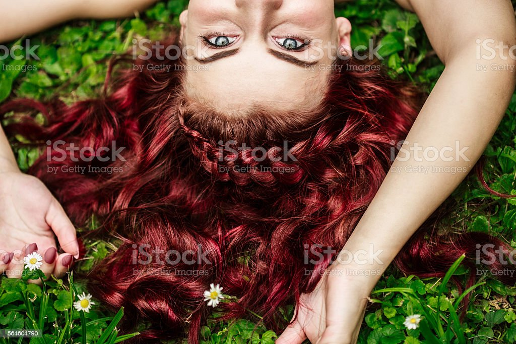 Young woman with redhead lying on grass stock photo