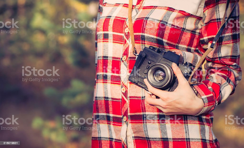 Young Woman with retro photo camera and plaid shirt outdoor stock photo