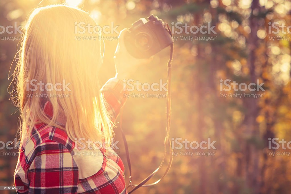 Young Woman with retro photo camera taking selfie shot outdoor stock photo