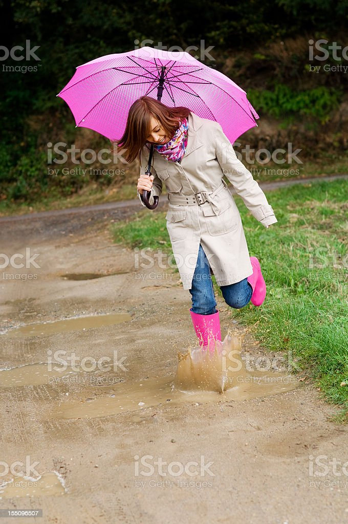 Young woman with rubber boots jumping in puddle royalty-free stock photo