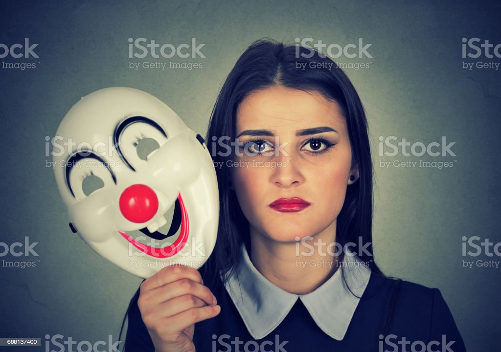 Young woman with sad face expression holding clown mask stock photo