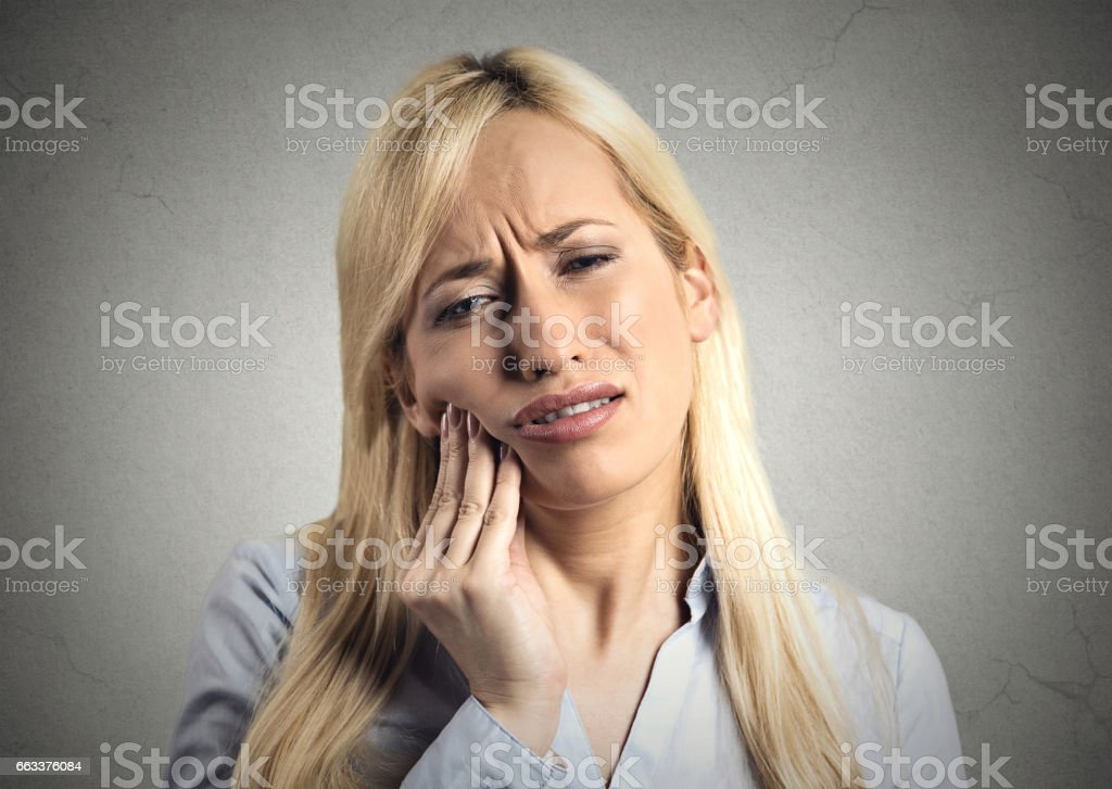 young woman with sensitive tooth ache crown problem about to cry from pain touching outside mouth with hand stock photo