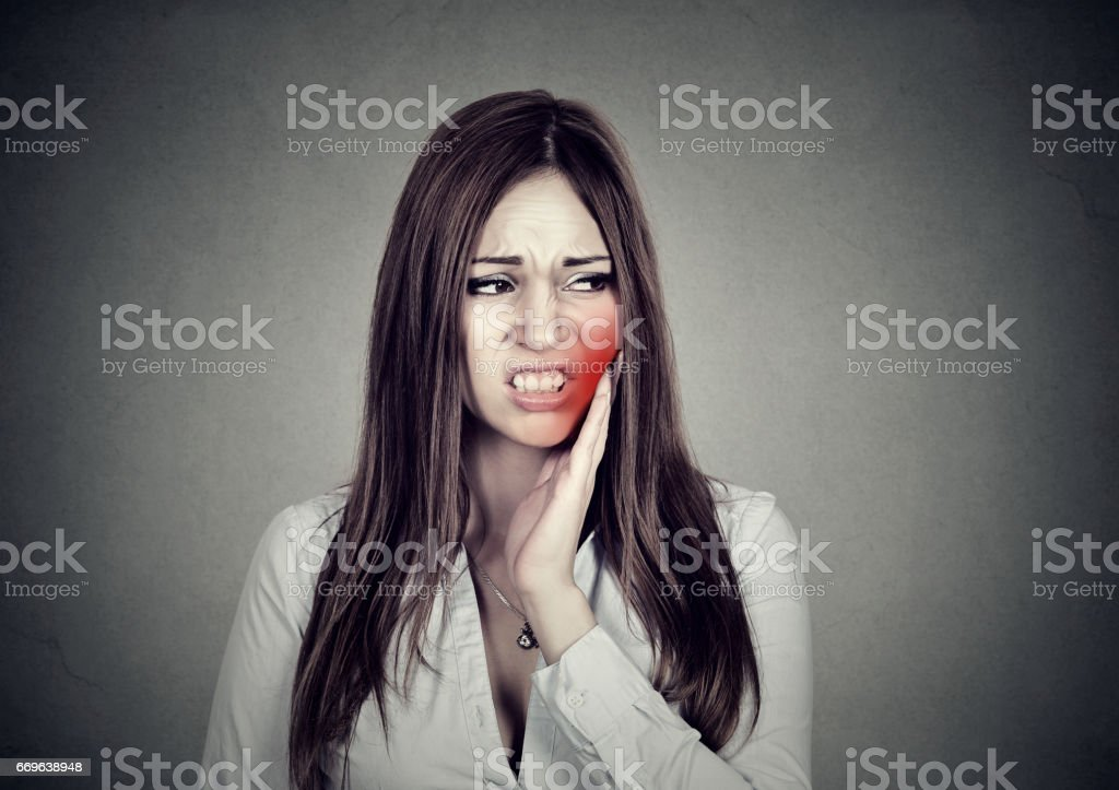 Young woman with sensitive toothache crown problem suffering from pain touching outside mouth with hand stock photo