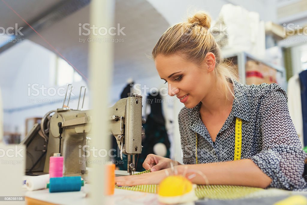 Young woman with sewing machine stock photo