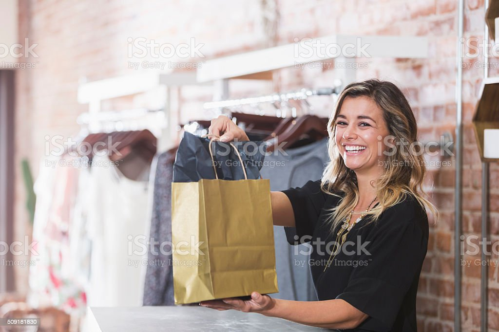 Young woman with shopping bag in clothing store stock photo