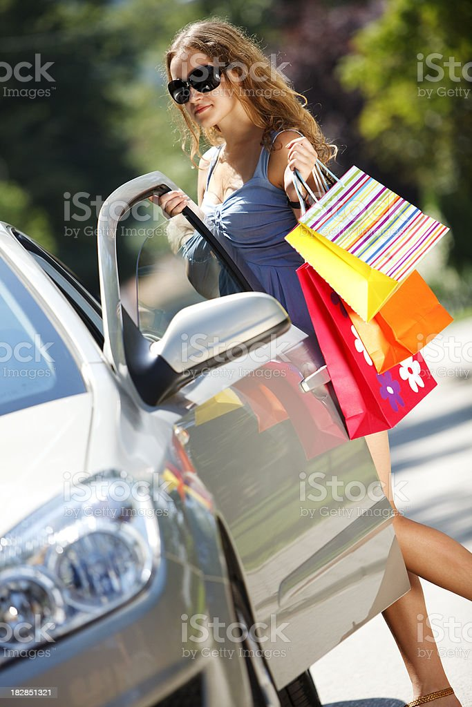 Young woman with shopping bags entering car royalty-free stock photo