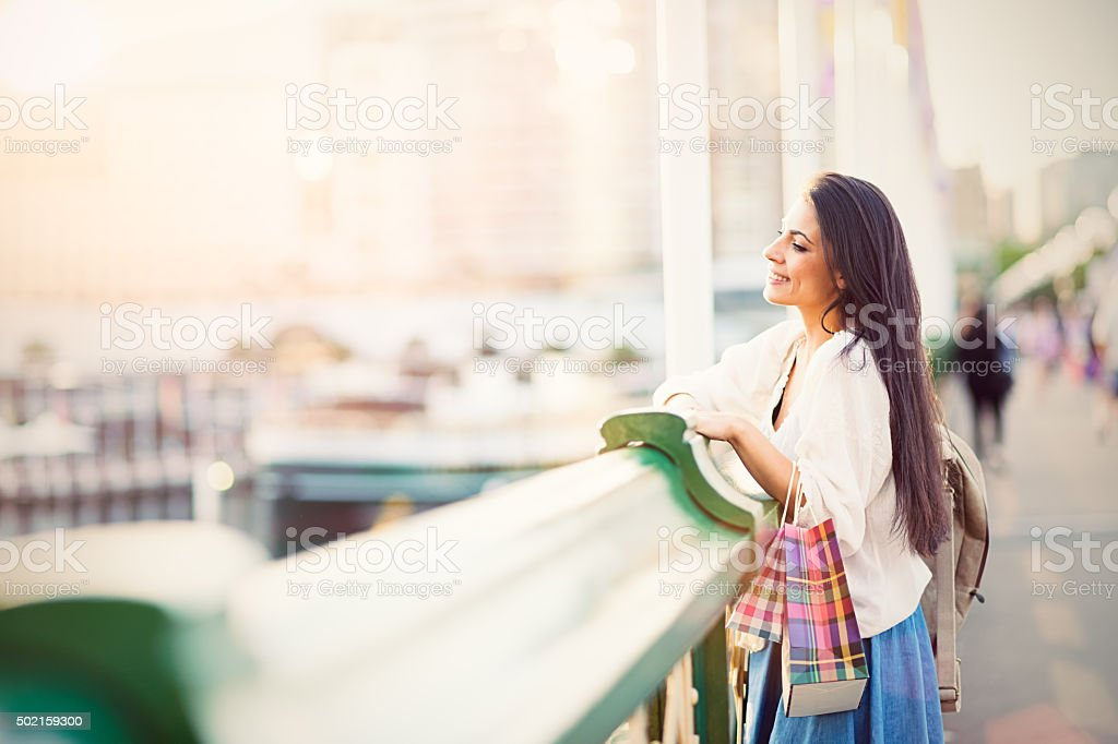 Young woman with shopping bags looking at Darling Harbor, Sydney stock photo