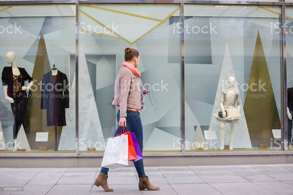 Young woman with shopping bags looking at window display stock photo