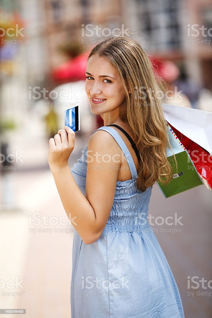 Young woman with shopping bags showing credit card royalty-free stock photo