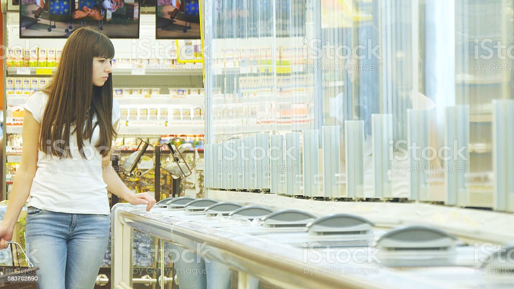 Young woman with shopping cart buying dairy or refrigerated groceries foto de stock libre de derechos