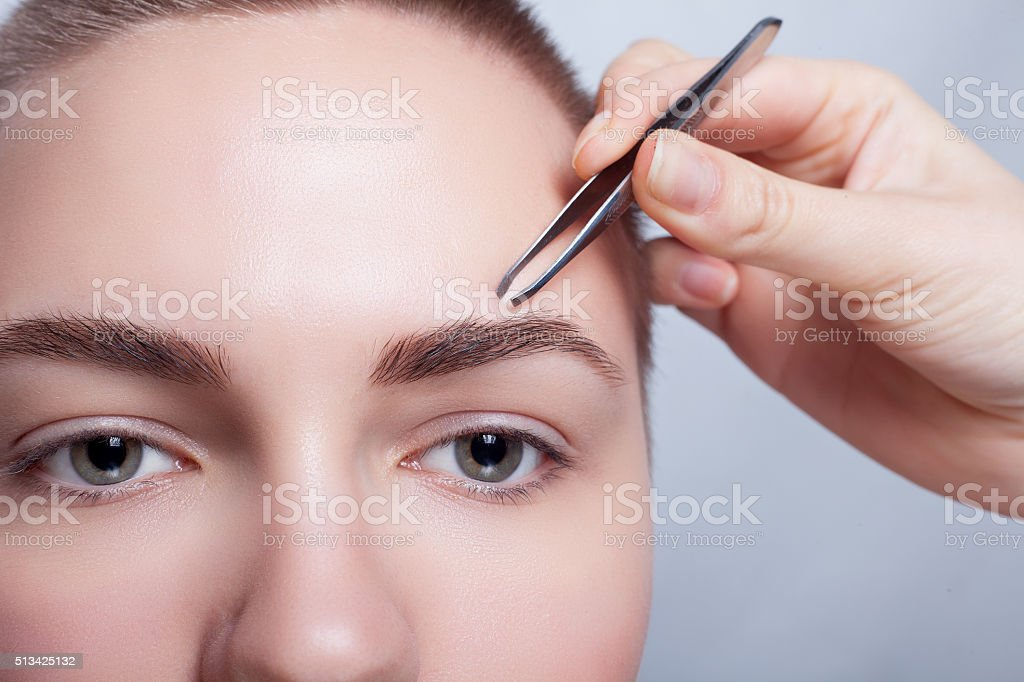 Young woman with short hair plucking eyebrows tweezers close up stock photo