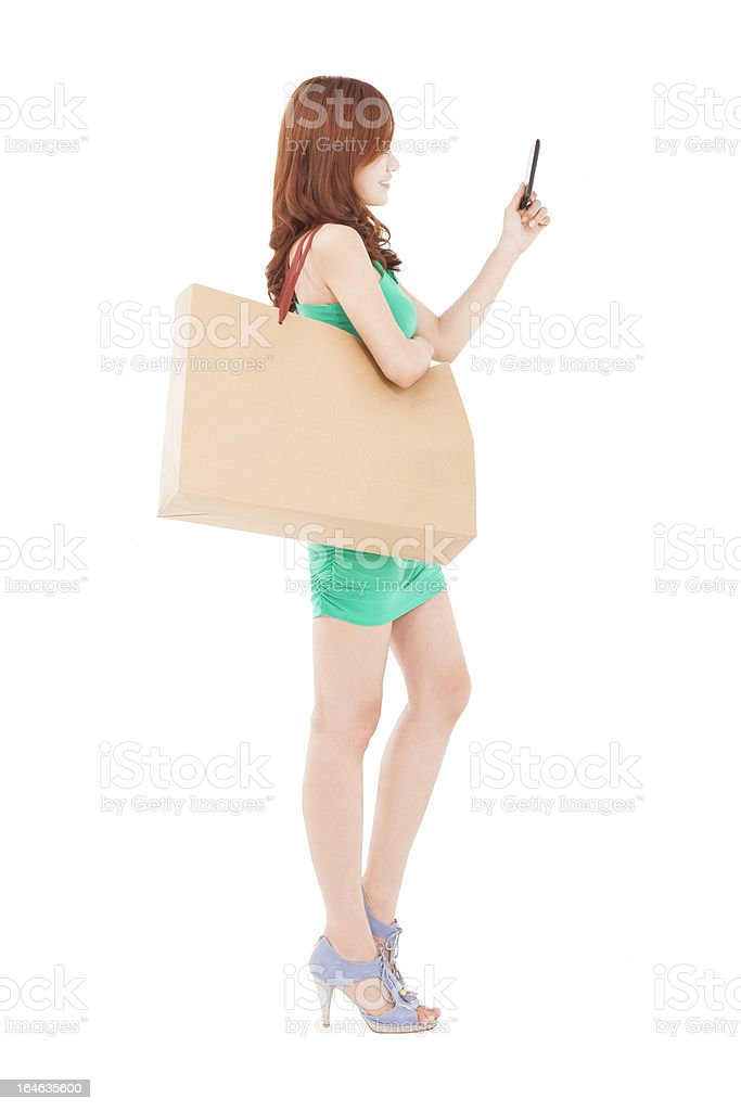 young woman with smart phone and shopping bag royalty-free stock photo