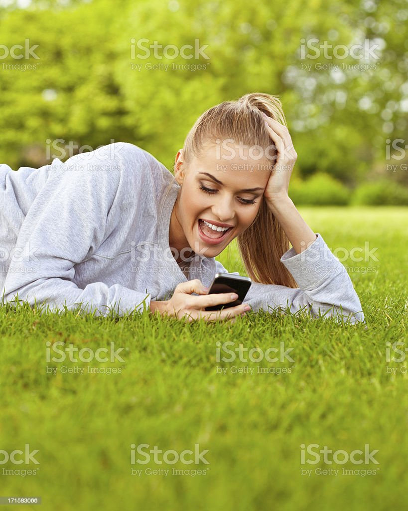 Young woman with smart phone in a park royalty-free stock photo