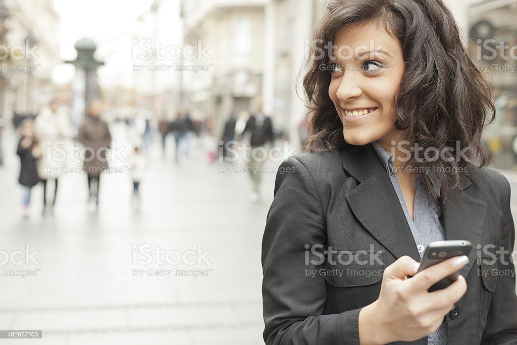 Young Woman with smartphone walking on street royalty-free stock photo