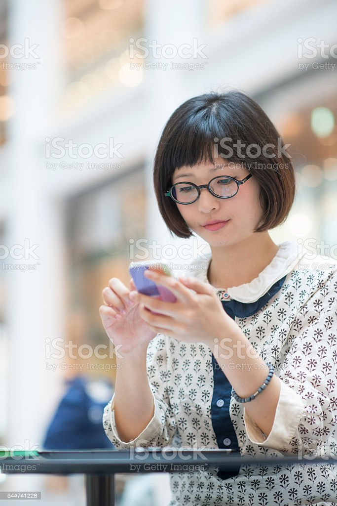 Young woman with spectacles using smartphone. stock photo