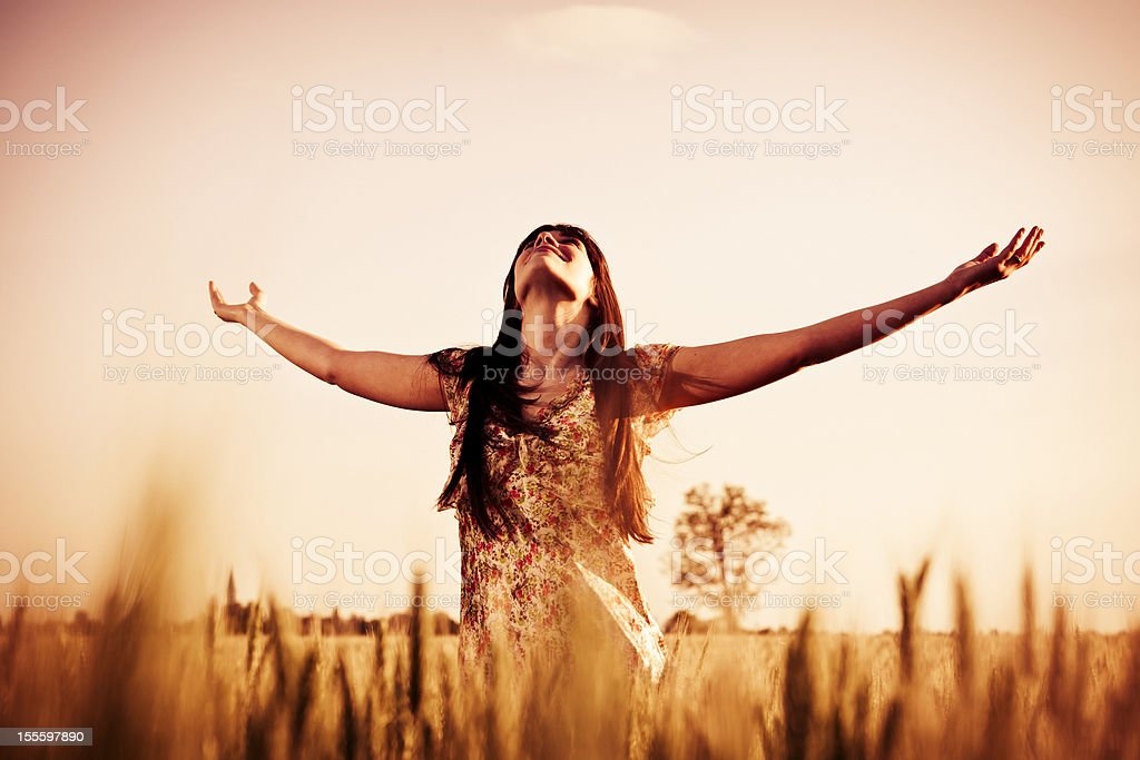 Young woman with spread arms looking up royalty-free stock photo