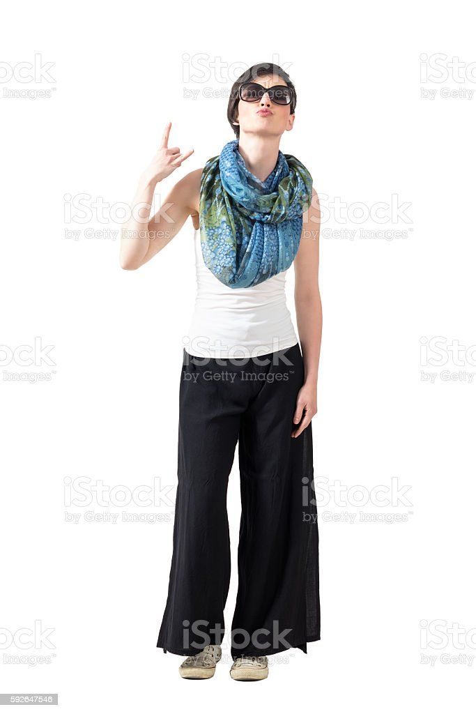 Young woman with sunglasses and scarf showing devil horns sign stock photo